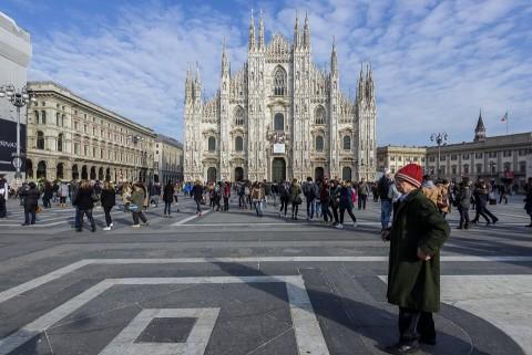 Hombre pasea por la plaza Duomo de Milan con la catedral de fondo
