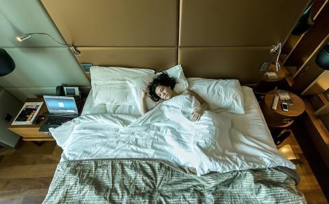 Chica asiática melancolica mirando por la ventana de una habitacion de hotel