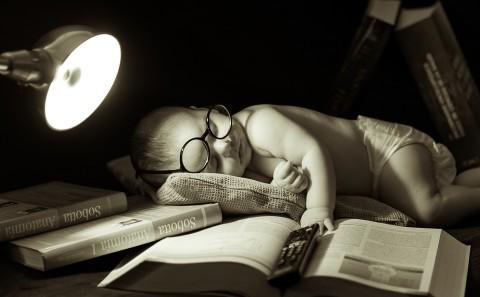 sesión de fotos con bebe, niño durmiendo simulando que está estudiando