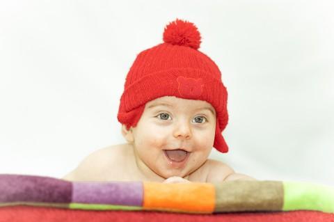 Sesión de fotos de estudio con bebe, bebe intenta levantarse con un gorro rojo