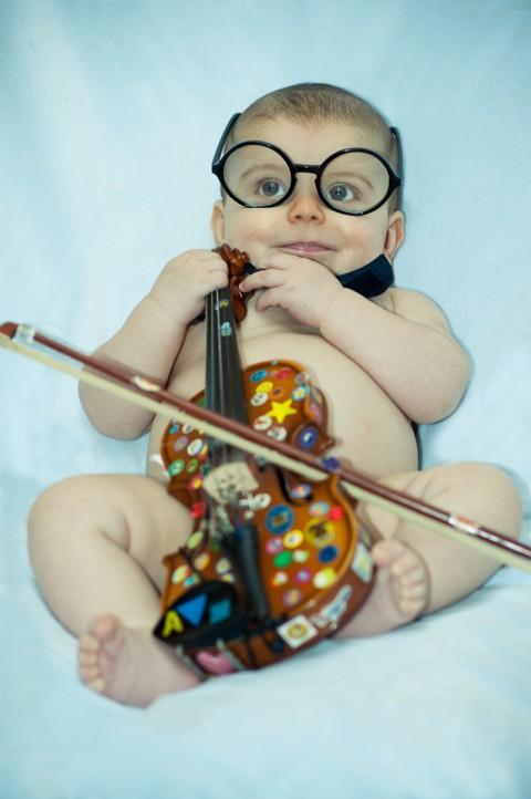 Sesión de fotos con bebe, el niño simula estar tocando el violin