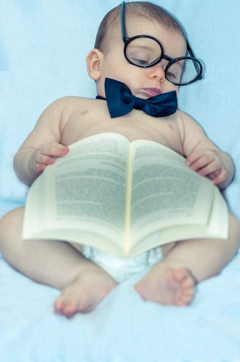 Sesión de fotos con bebe, el niño simula estar leyendo un libro