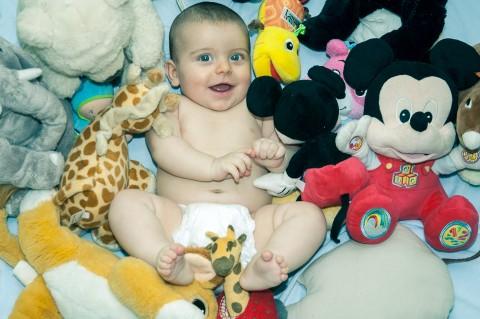 Sesión de fotos de bebe rodeado de peluches y sonrie