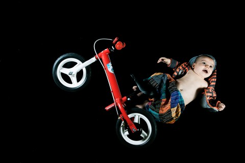 sesión de fotos de estudio, bebe simula saltar con una bici