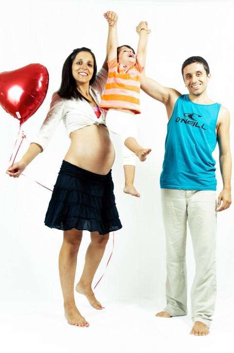 Familia jugando con su hijo mayor en sesión de embarazo
