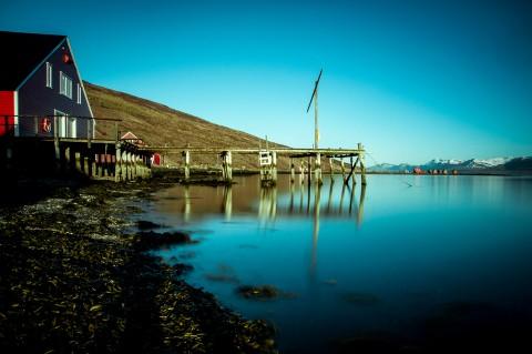 Fiordos del este en Islandia, casa roja y muelle sobre el lago