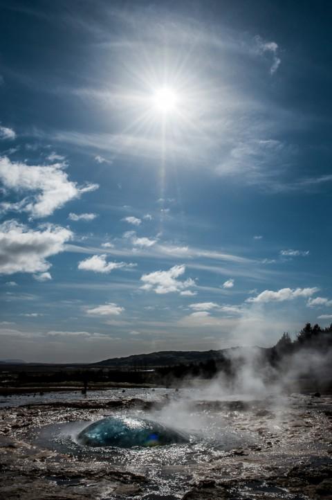 geiser de islandia con el sol de fondo