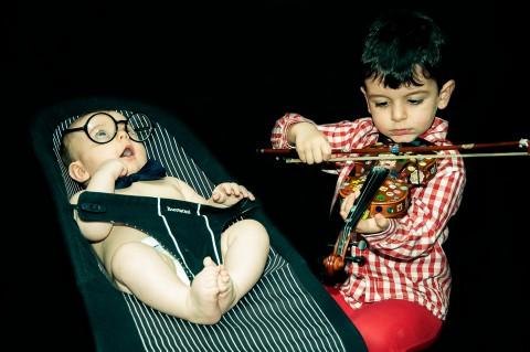 Sesión de estudio, hermano mayor toca el violín al hermano pequeño