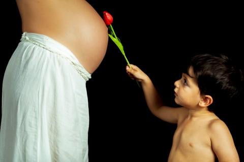 Hermano ofreciendo rosa a hermano en barriga de mama