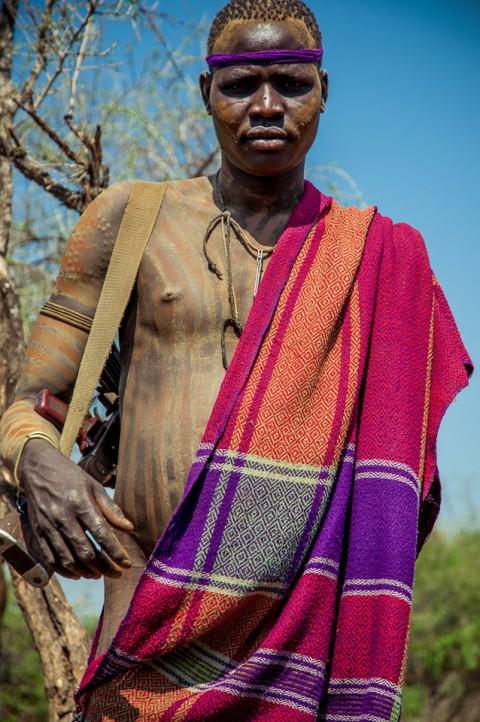 Hombre de tribu Mursi armado con rifle y desnudo, Etiopía