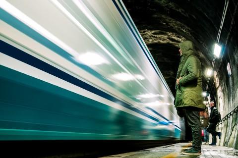 Hombre con capucha esperando tren en anden