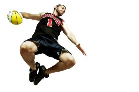 Sesión de estudio, jugador de baloncesto salta para hacer un mate