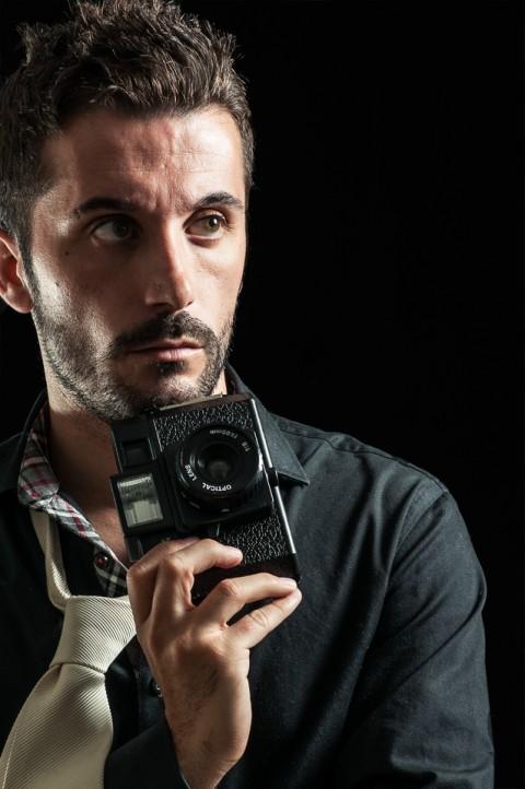 Hombre modelo con camara de fotos, sesión de estudio