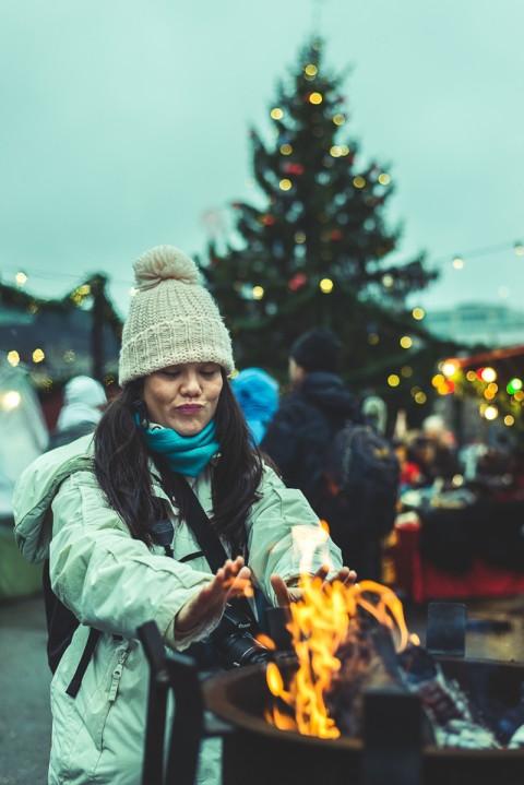 Mujer se calienta las manos en Fuego durante la navida
