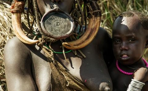 Mujer de la tribu Mursi con hijo y plato en el labio, Etiopía