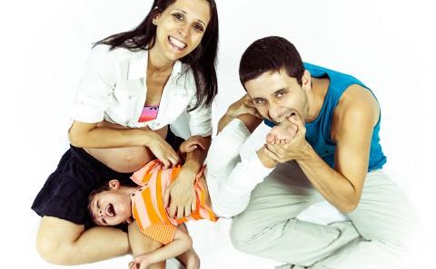 Sesión de fotos de embarazo, padres juegan con hijo mayor