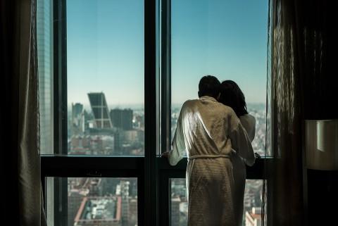 Pareja mirando Madrid a través de la ventana del Hotel Eurostars, torre de Madrid